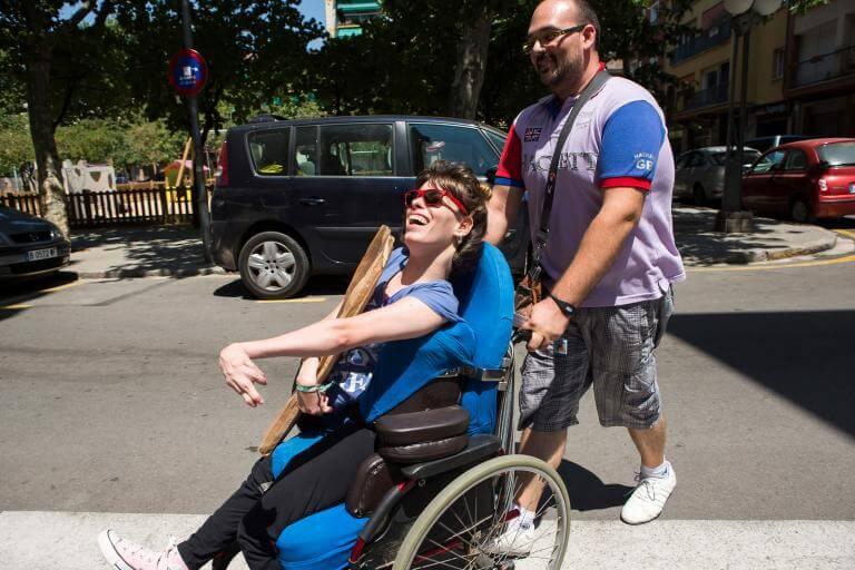 Una noia amb discapacitat física travessant un carrer acompanyada pel seu assistent personal