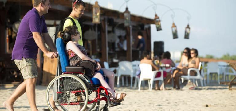 Dos chicos acompañando a una chica con discapacidad física a la playa
