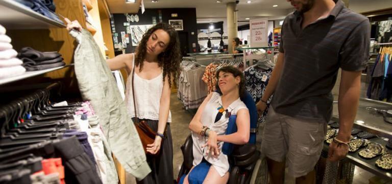 Una chica y un chico comprando en una tienda de ropa con una chica en silla de ruedas