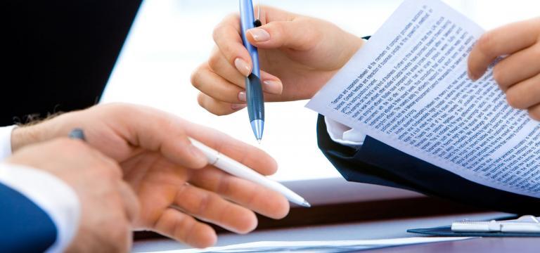 Primer pla de dues mans de dues persones diferents amb papers i bolígrafs a les mans; com si estiguessin contrastant informació