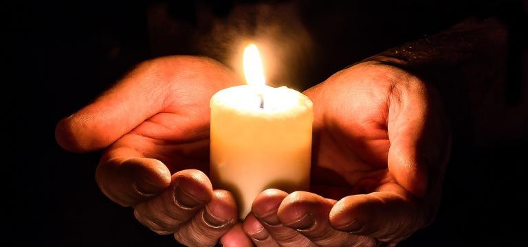 Dues mans en posició d'oferiment, sostenint, oferint una espelma