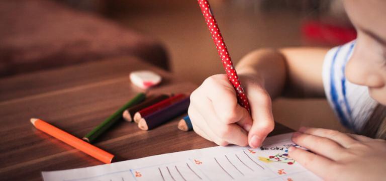 Un muchacho escribiendo con un lápiz en un papel