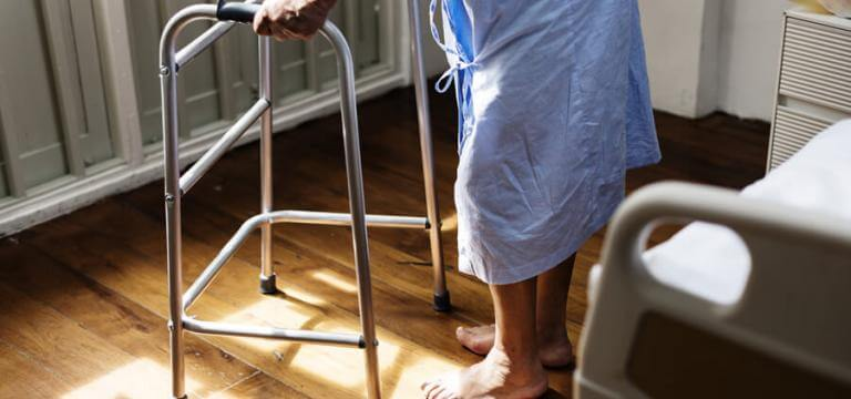 Un anciana de pie ante la cama ayudándose de un andador