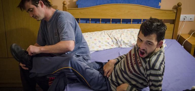 Un hombre ayudando a un chico a vestirse en la cama