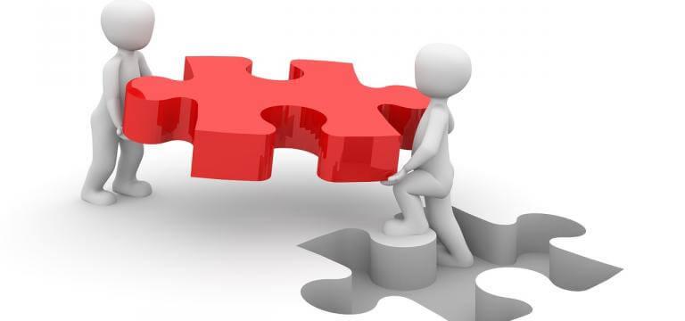 Imagen de dos muñecos -que simulan personas- llevando una pieza de puzzle a encajar en un espacio donde encaja