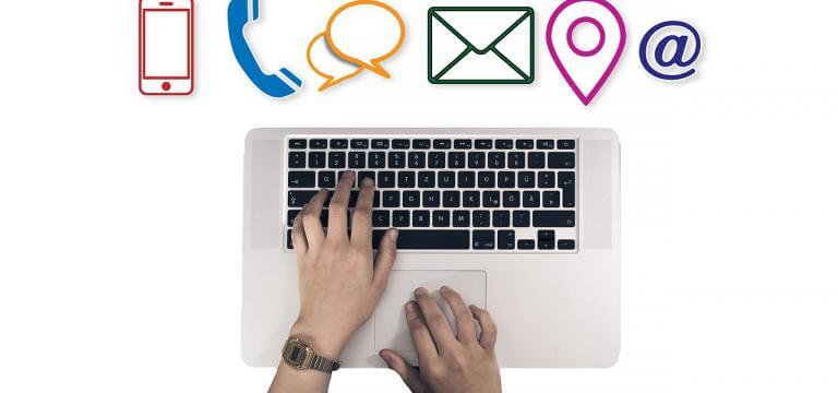 El teclado de un ordenador con unas manos trabajando y sobre esta imagen hay diferentes iconos: un teléfono fijo, un teléfono móvil, un sobre (dirección postal), el símbolo de la ubicación...