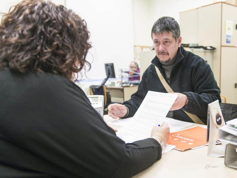 Una tècnica d'ECOM d'esquenes asseguda en una taula atenent a una persona que asseguda al davant d'ella li mostra un paper
