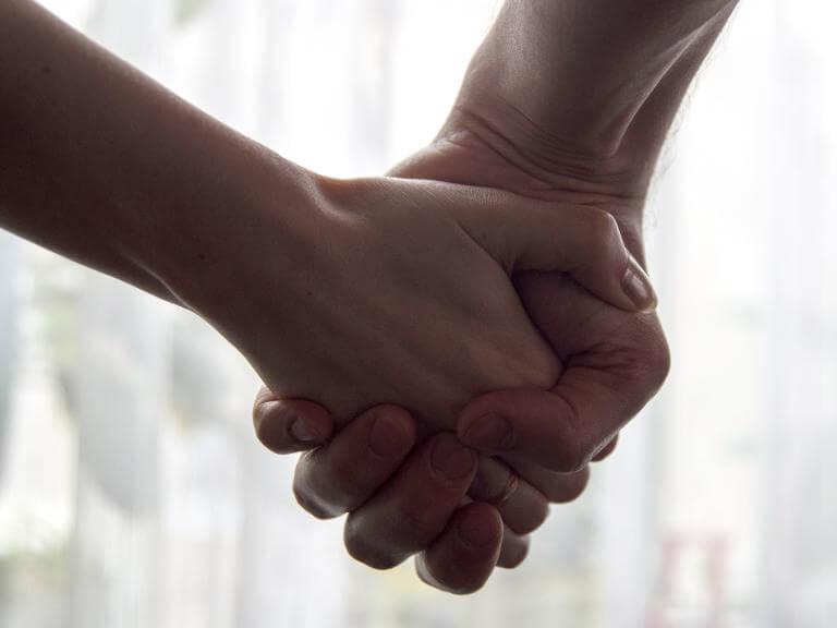Primer plano de dos manos cogidas en símbolo de amistad