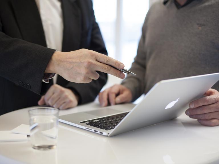 Dos hombres mirando un ordenador, uno de ellas en actitud de estar explicando algo al otro