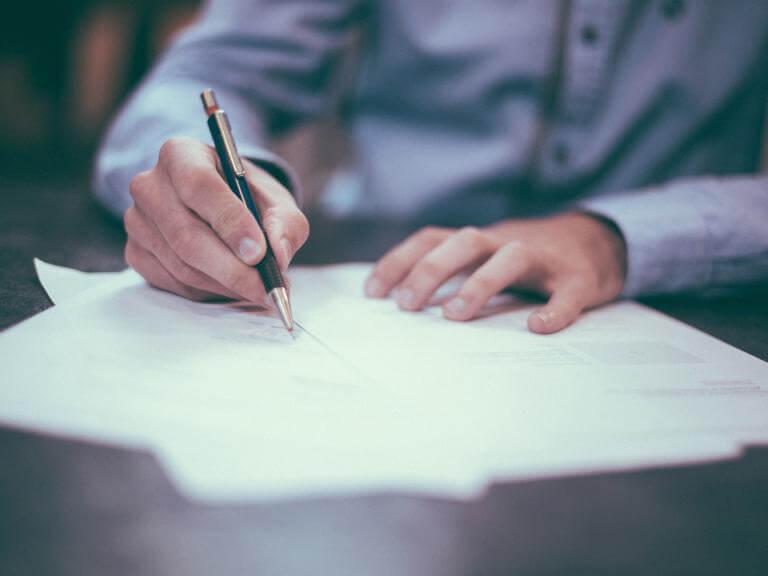 Las manos de una persona rellenando unos documentos con bolígrafo