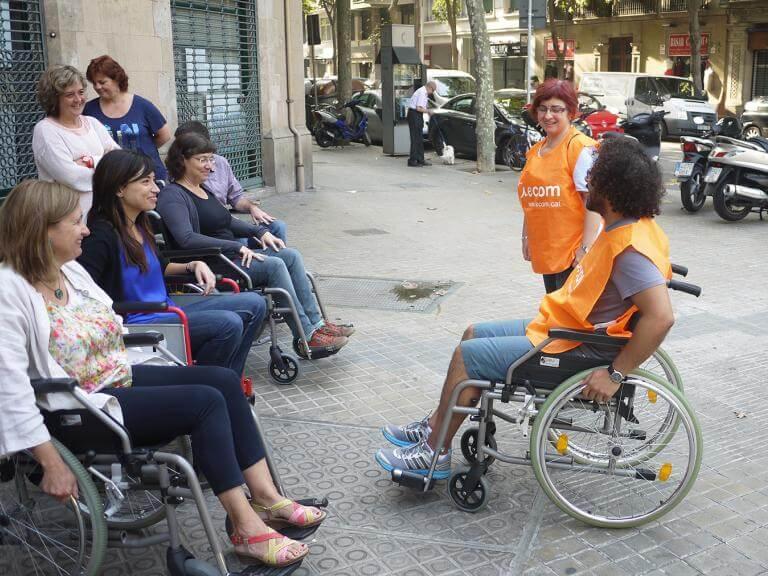 Dos técnicos de ECOM (uno de ellos sentado en una silla de ruedas) da explicaciones a profesionales de una empresa que están sentadas en sillas de ruedass preparadas para hacer una ruta por la calle de una ciudad