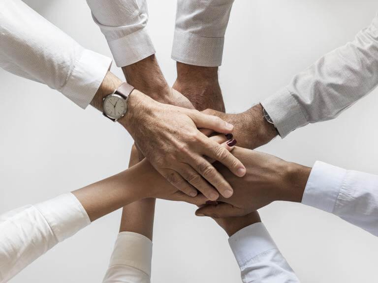 Las manos de diversas personas puestas unas encima de otras como expresando suma de fuerzas