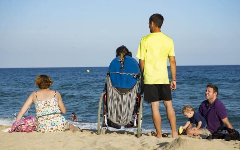 Una persona usuària de cadira de rodes a la platja, acompanyada pel seu assistent personal i altres persones