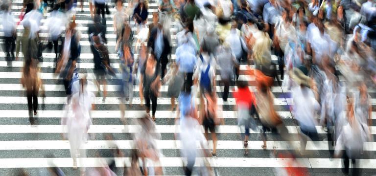 Imagen difuminada de muchas personas cruzando un paso de cebra
