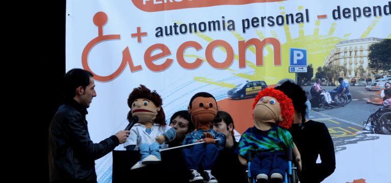 Escenari on estan s'està representant l'espectacle de titelles d'ECOM, davant una pancarta reivindicativa on s'identifica que és el Dia Internacional de la Discapacitat