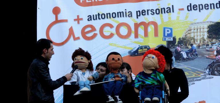 Escenario con una actuación de los títeres de ECOM con un fondo de escenario que es una pancarta reivindicativa en el Día Internacional de la Discapacidad
