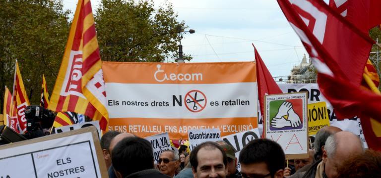 Una pancarta d'ECOM en primer pla enmig d'una manifestació