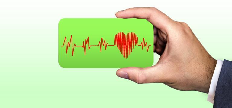 Una mà sostè una petita pantalla on es veuen les pulsacions del cor