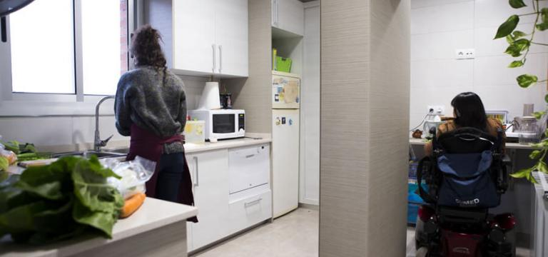 Dues noies a una cuina, una d'elles en cadira de rodes davant una taula i l'altre dempeus davant l'aigüera