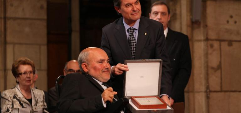 Imatge d'un dels presidents d'ECOM recollint la Creu de Sant Jordi de mans del qui va ser president de la Generalitat de Catalunya,Artur Mas