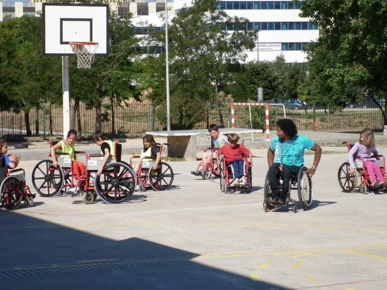Alumnes al pati d'una escola asseguts a cadires de rodes i atenent les instruccions d'un noi amb discapacitat (també usuari de cadira de rodes) sobre com ho han de fer per moure's en la cadira