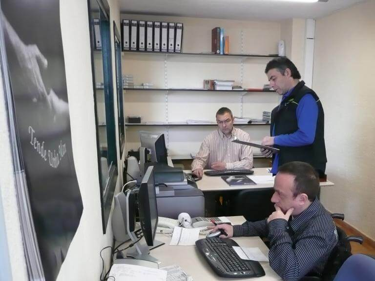 Tres persones en un despatx treballant, una d'elles usuària de cadira de rodes, que està treballant amb l'ordinador