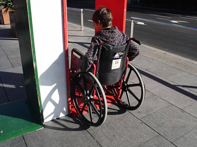 Un joven sentado en una silla de ruedas intentando pasar por una estructura que simula la entrada de una puerta. La imagen muestra dos opciones de entrada (o puerta) una pintada de verde, que es accesible, y una roja (que es demasiado estrecha, aunque permite el paso).