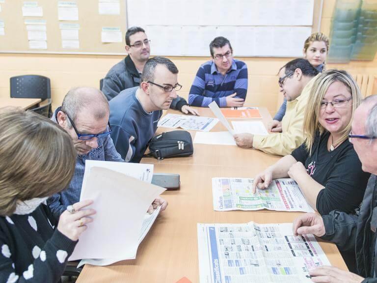 Diversas personas con discapacidad consultando anuncios de trabajo en la prensa