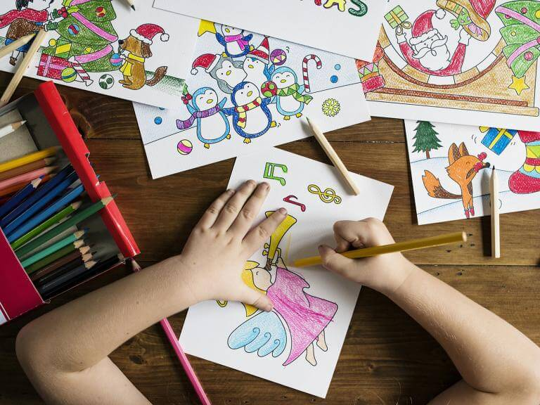 Las manos de una niña haciendo dibujos sobre una mesa llena de dibujos y colores